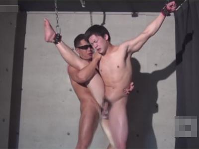 【ゲイ動画】立たされた状態で拘束をされている細身の男がゴーグルマンにアナルセックスをされて果てることになる!
